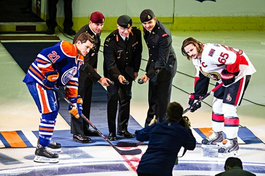 Members of the military take part in the ceremonial puck drop during Canadian Armed Forces Appreciation Night during the Edmonton Oilers' NHL hockey game against the Ottawa Senators at Rexall Place in Edmonton, Alta., on Thursday, Nov. 13, 2014. Codie McLachlan/Edmonton Sun/QMI Agency