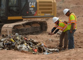 Workers take photos of recovered Atari games at the old Alamogordo landfill in Alamogordo, New Mexico, April 26, 2014. REUTERS/MARK WILSON