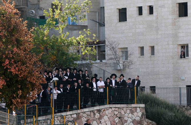 Onlookers stand near the scene of an attack at a Jerusalem synagogue November 18, 2014. Two Palestinians armed with a meat cleaver and a gun killed four people in a Jerusalem synagogue on Tuesday before being shot dead by police, the deadliest such incident in six years in the holy city amid a surge in religious conflict. REUTERS/Ammar Awad