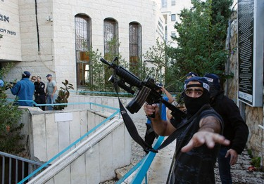 An Israeli police officer gestures as he holds a weapon near the scene of an attack at a Jerusalem synagogue November 18, 2014. Two suspected Palestinian men armed with axes and knives killed four people in a Jerusalem synagogue on Tuesday before being shot dead by police, Israeli police and emergency services said, the deadliest such attack in the city in years. REUTERS/Ronen Zvulun