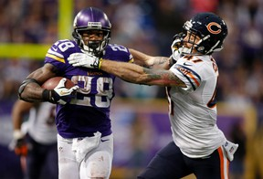 Minnesota Vikings running back Adrian Peterson (28) pushes off Chicago Bears safety Chris Conte in this December 1, 2013 file photo in Minneapolis, Minnesota. (Bruce Kluckhohn/USA TODAY Sports/Files)