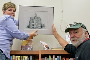Ches Sulkowski (right) sets up his art exhibition at the Tillsonburg Public Library (OCL) Wednesday afternoon. The six-week show, which includes 11 sketches of historical Tillsonburg buildings, is being offered by Oxford Creative Connections Inc., which features artists from around Oxford County. Helping Sulkowski set up is Mary-Anne Murphy, Oxford Creative Connections Inc. cultural coordinator. (CHRIS ABBOTT/TILLSONBURG NEWS)