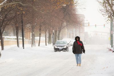 A woman walks down the middle of the street through the blowing snow in Buffalo, N.Y., on November 19, 2014. (REUTERS/Lindsay DeDario)