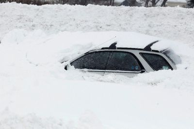 A vehicle is shown submerged in snow sits on interstate I-190 in West Seneca, New York November 19, 2014. REUTERS/Sharon Cantillon/Buffalo News/Pool