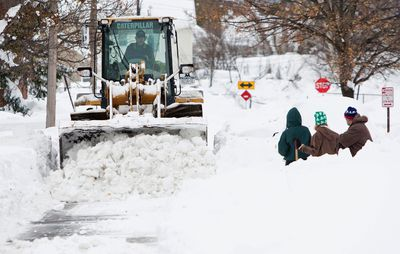 Heavy machinery clears snow from a street following an autumn storm in Buffalo, New York, November 20, 2014. REUTERS/Aaron Lynett