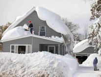 A man clears snow from his roof in the town of Cheektowaga near Buffalo, New York, November 19, 2014. An autumn blizzard dumped a year's worth of snow in three days on Western New York state, where at least 10 people died. REUTERS/Lindsay DeDario