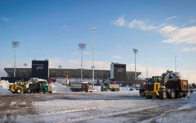 Snow is cleared outside of Ralph Wilson Stadium in Buffalo, New York, November 21, 2014. Some areas of New York state along the Great Lakes had around 2 feet (60 cm) of new snow on Thursday on top of accumulations as deep as 5 feet from earlier in the week. The National Weather Service said parts of the region could expect 3 feet more snow before skies clear on Friday.  REUTERS/Aaron Ingrao