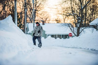 A man with a shovel looks at a tall snowbank in Buffalo, New York, November 21, 2014. Some areas of New York state along the Great Lakes had around 2 feet (60 cm) of new snow on Thursday on top of accumulations as deep as 5 feet from earlier in the week. The National Weather Service said parts of the region could expect 3 feet more snow before skies clear on Friday.  REUTERS/Aaron Ingrao