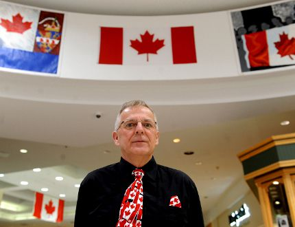 Bob Harper, chairman of the 50 Years of Our Flag committee, stands beneath some of the murals honouring the late John R. Matheson at the 1000 Islands Mall (Recorder and Times file photo).