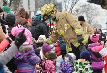 Firefighters hand out candy during the Help Santa Toy Parade in Ottawa on Saturday, Nov. 22, 2014. Matthew Usherwood/Ottawa Sun