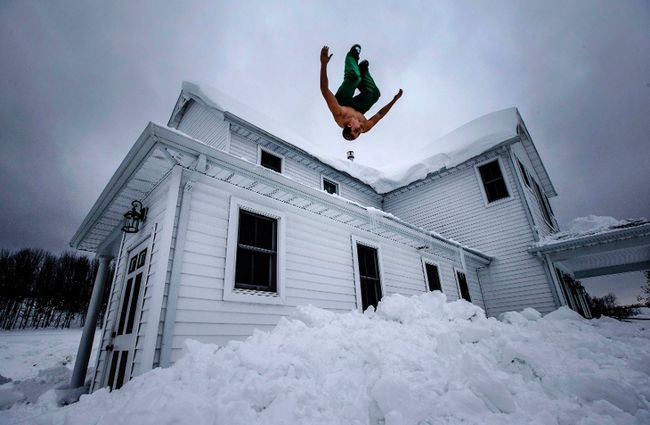 Phil Mohun does a back flip off of his family home after clearing snow from the roof following a massive snowstorm in Cowlesville, N.Y., on November 22, 2014. (REUTERS/Mark Blinch)