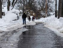 People walk down a street flowing with water after a water main broke in Buffalo, N.Y., on November 22, 2014. (REUTERS/Mark Blinch)