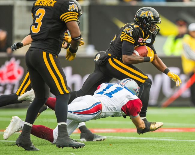 Hamilton Tiger-Cats Terrell Sinkfield and Montreal Alouettes Chip Cox at Tim Hortons Field during the 1st half of the CFL Eastern Final in Hamilton, Ont. on Sunday November 23, 2014. (Ernest Doroszuk/QMI Agency)