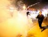 Protesters run from a cloud of tear gas after a grand jury returned no indictment in the shooting of Michael Brown in Ferguson, Missouri
