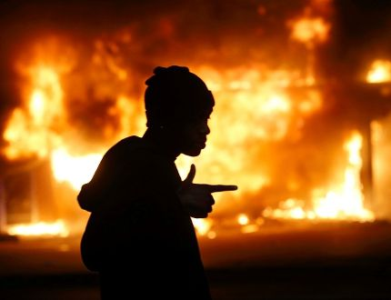 A man walks past a burning building during rioting after a grand jury returned no indictment in the shooting of Michael Brown in Ferguson, Mo., on November 24, 2014. (REUTERS/Jim Young)