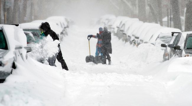 People clear snow from around vehicles during the snowstorm that hit Montreal on Sunday, December 15, 2013. (Joel LemayQMI Agency)