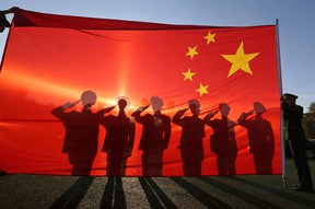 Retired paramilitary policemen, who conduct the daily national flag raising and lowering ceremony on Tiananmen Square, salute to a Chinese national flag during a farewell ceremony in Beijing, November 24, 2014. (REUTERS/Stringer)