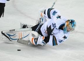 Goalie Alex Stalock from the San Jose Sharks has a moment as he tries to clear the puck against the Calgary Flames in NHL hockey action at the Saddledome in Calgary on March 24, 2014. (Stuart Dryden/Calgary Sun/QMI Agency)