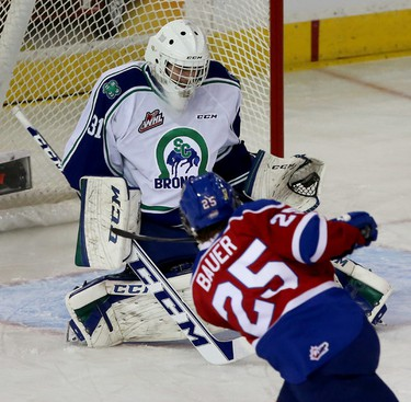 Swift Current Broncos goalie Travis Child makes a glove save off of  Edmonton Oil Kings Lane Bauer during first period action at Rexall Place in Edmonton Alta.,  on Wednesday Nov 26, 2014. Child  was brought into the game after the starting goalie let in two goals. Tom Braid/Edmonton Sun/QMI Agency