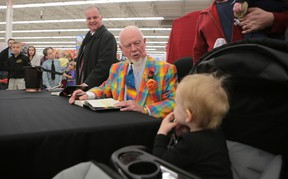 Hockey commentator Don Cherry says hello to Grace George, 2, at Walmart during a book signing Thursday night. (Elliot Ferguson/The Whig-Standard)