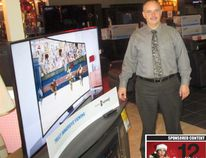Brad Schott, owner of Leon's in downtown Simcoe, with a curved-screen television. (CHRIS THOMAS photo)