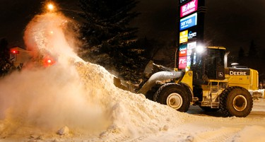 Snow flies as a front-end loader works on clearing snow out of the Marketplace at Callingwood parking lot at 69 Ave., and 178 St., Thursday evening Nov. 27, 2014 in Edmonton Alta. Tom Braid/Edmonton Sun/QMI Agency