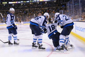 Winnipeg Jets center Bryan Little (18) is helped up by teammates left wing Andrew Ladd (16) and right wing Blake Wheeler (26) during the third period against the Boston Bruins on Friday. The Jets say the injury isn't serious. (Bob DeChiara-USA TODAY Sports)