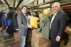Mohamed (Moe) El Tassi (left), and his father Albert (Abdo) El Tassi, with some of the clothing items donated to Siloam Mission by the El Tassi family. (Chris Procaylo/Winnipeg Sun)