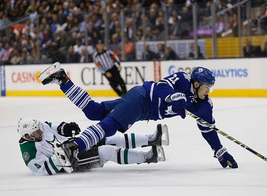 James van Riemsdyk battles with Jason Demers of Dallas as the Toronto Maple Leafs host the Dallas Star in an NHL regular season game at the Air Canada Centre in Toronto on Tuesday December 2, 2014. Michael Peake/Toronto Sun/QMI Agency