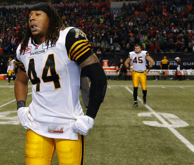 Dejected Hamilton Tiger-Cats Taylor Reed and Arnaud Gascon-Nadon walk off the field after losing 102nd Canadian Football League Grey Cup to the Calgary Stampeders 20-16 in Vancouver on Nov. 30, 2104. (Al Charest/Calgary Sun/QMI Agency)