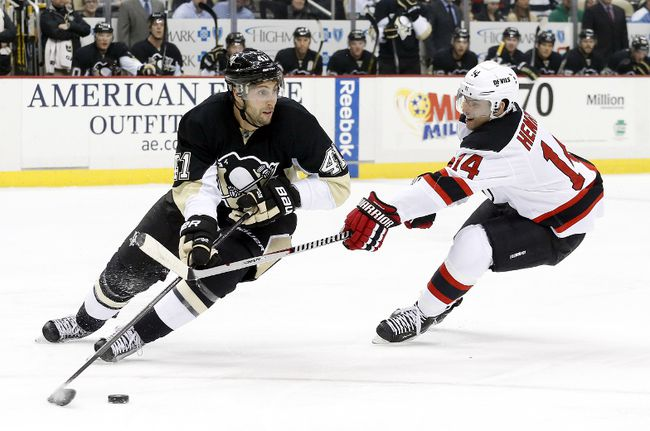 Pittsburgh Penguins defenseman Robert Bortuzzo (41) handles the puck against pressure from New Jersey Devils center Adam Henrique (14) during the first period at the CONSOL Energy Center on Dec 2, 2014. Charles LeClaire-USA TODAY Sports