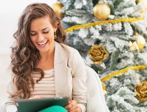 Happy young woman using tablet pc near christmas tree