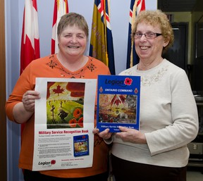 Bonnie Axcell, President of The Cochrane Royal Canadian Legion and Dorothy Smith Ladies' Auxiliary President pose with Ontario Command Military Service Recognition Book Volume 1 at the Cochrane Legion.