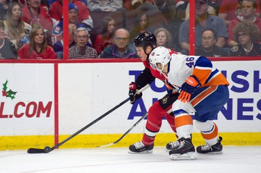 Dec 4, 2014; Ottawa, Ontario, CAN; Ottawa Senators right wing Chris Neil (25) and New York Islanders defenseman Matt Donovan (46) battle for the puck in the second period at the Canadian Tire Centre. Mandatory Credit: Marc DesRosiers-USA TODAY Sports