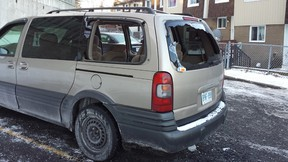A van sits in a Penny Dr. driveway after having its windows shot out during what residents called a gunfight Thursday night in the Britannia townhome complex. Two men suffered gunshot wounds and are in hospital. (COREY LAROCQUE Ottawa Sun)