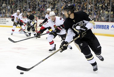 Dec 6, 2014; Pittsburgh, PA, USA; Pittsburgh Penguins center Brandon Sutter (16) handles the puck as Ottawa Senators center Kyle Turris (7) pressures during the first period at the CONSOL Energy Center. The Penguins won 3-2. Mandatory Credit: Charles LeClaire-USA TODAY Sports