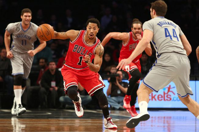 Chicago Bulls point guard Derrick Rose (1) dribbles the ball in front of Brooklyn Nets center Brook Lopez (11) and shooting guard Bojan Bogdanovic (44) during the first quarter at Barclays Center on Nov 30, 2014; Brooklyn, NY, USA. (Brad Penner/USA TODAY Sports)