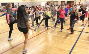 Students from the Fitness Leadership program at La Salle Secondary School lead Grades 4-6 students from Sir John A. Macdonald Public School in a warm-up prior to testing their fitness on Dec. 10. (Michael Lea/The Whig-Standard).
