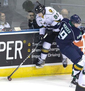 Knights forward Mitch Marner makes a cross-ice pass despite being knocked into the air by Plymouth Whalers? Cullen Mercer during the first period of their OHL game at Budweiser Gardens on Friday night. Marner?s London teammate Christian Dvorak accepted the pass and shot the puck past Whalers goalie Alex Nedelijkovic for a 1-0 lead. (DEREK RUTTAN, The London Free Press)
