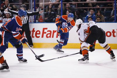 Edmonton centre Leon Draisaitl (29) passes the puck under pressure from Anaheim forward Rene Bourque (14) during the first period of a NHL hockey game between the Edmonton Oilers and Anaheim Ducks at Rexall Place in Edmonton, Alta., on Friday, Dec. 12, 2014. Ian Kucerak/Edmonton Sun/ QMI Agency