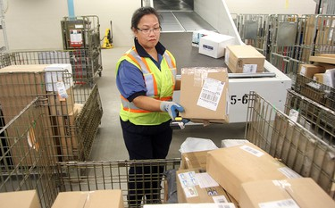 Canada Post worker Elizabeth Avad moves sorted packages for Winnipeg delivery at the main post office in Winnipeg, Man. Monday December 15, 2014. Brian Donogh/Winnipeg Sun/QMI Agency
