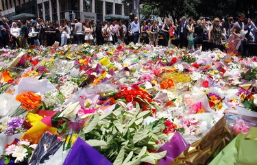 Members of the public look at floral tributes placed near the cafe where hostages were held for over 16-hours, in central Sydney December 16, 2014.   REUTERS/David Gray