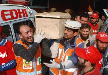Rescue workers and family members carry the coffin of a student, who was killed during an attack by Taliban gunmen on the Army Public School, in Peshawar, December 16, 2014. (REUTERS/Khuram Parvez)