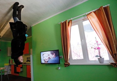 A woman visits a room in a house built upside-down in Russia's Siberian city of Krasnoyarsk, December 14, 2014. The house was constructed as an attraction for local residents and tourists. Picture rotated 180 degrees. REUTERS/Ilya Naymushin