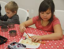 Brodie Sherk, 4, and Taryn Loonskin, 7, make wreaths from pipe cleaners and beads at the Grande Prairie Museum on Tuesday. LAURA BOOTH /DAILY HERALD-TRIBUNE/QMI AGENCY