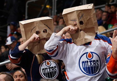 GLENDALE, AZ - DECEMBER 16: Fans of the Edmonton Oilers wearing bags on their heads react during the NHL game against the Arizona Coyotes at Gila River Arena on December 16, 2014 in Glendale, Arizona. The Coyotes defeated the Oilers 2-1 in an overtime shootout.   Christian Petersen/Getty Images/AFP == FOR NEWSPAPERS, INTERNET, TELCOS & TELEVISION USE ONLY ==