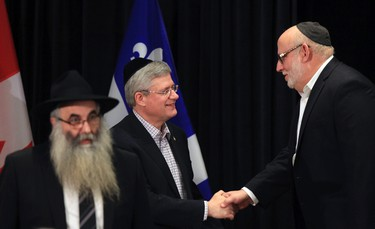 Canada's Prime Minister Stephen Harper (C) shakes hands with Rabbi Reuben Poupko (R) and Rabbi Shalom Chriqui as he participates in a candle lighting ceremony to mark the start of Hanukkah in Montreal,  Quebec, December 16, 2014.   REUTERS/Christinne Muschi