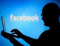 A man is silhouetted against a video screen with a Facebook logo as he poses with a laptop in this photo illustration taken in the central Bosnian town of Zenica in this August 14, 2013 file photo. (REUTERS/Dado Ruvic/Files)