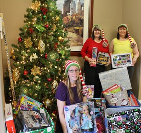Midhaven Homes collected over 200 gifts for a Christmas Toy Drive, new home owners gave generously to the cause. From left: Midhaven's Kristina Petrie, new Midhaven home owner Vicki Johnson, and Midhaven's Rebecca Evans prepare to wrap and deliver the toys.