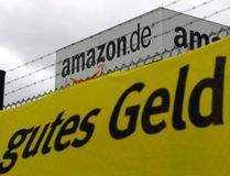 "Verdi union placard reading ""good money"" is placed in front of the Amazon logistics centre in Graben near Augsburg Dec. 15, 2014. REUTERS/Michaela Rehle"